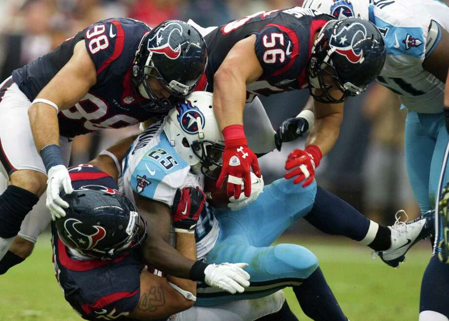 Houston Texans nose tackle Shaun Cody (95), linebacker Connor Barwin (98) and inside linebacker Brian Cushing (56) stop Tennessee Titans wide receiver Darius Reynaud (25) during the third quarter at Reliant Stadium on Sunday, Sept. 30, 2012, in Houston. The Texans beat the Titans 38-14. Photo: Brett Coomer, Houston Chronicle / © 2012  Houston Chronicle
