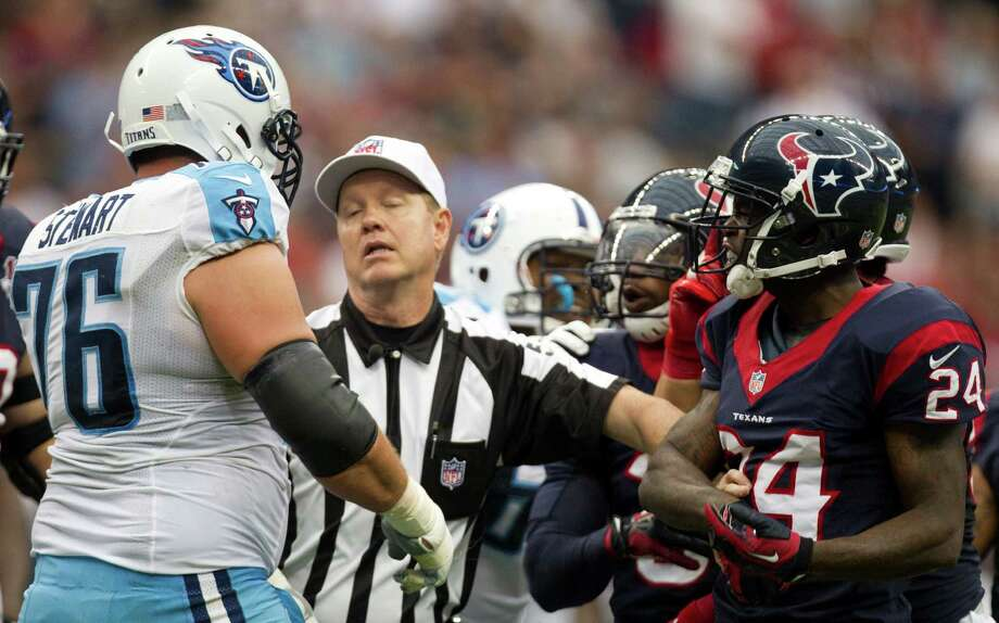Referee Carl Cheffers, center, steps between Tennessee Titans tackle David Stewart (76) and Houston Texans cornerback Johnathan Joseph (24) during the third quarter at Reliant Stadium on Sunday, Sept. 30, 2012, in Houston. The Texans beat the Titans 38-14. Photo: Brett Coomer, Houston Chronicle / © 2012  Houston Chronicle
