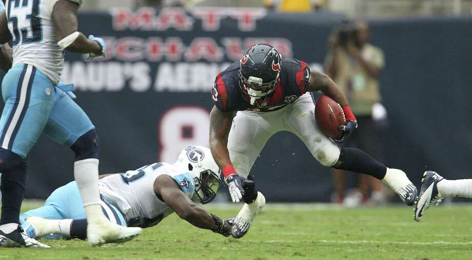 Houston Texans running back Arian Foster (23) gains yardage against  Tennessee Titans outside linebacker Zach Brown (55) during the fourth quarter at Reliant Stadium on Sunday, Sept. 30, 2012, in Houston. Texans won 38-14. Photo: Karen Warren, Houston Chronicle / © 2012  Houston Chronicle