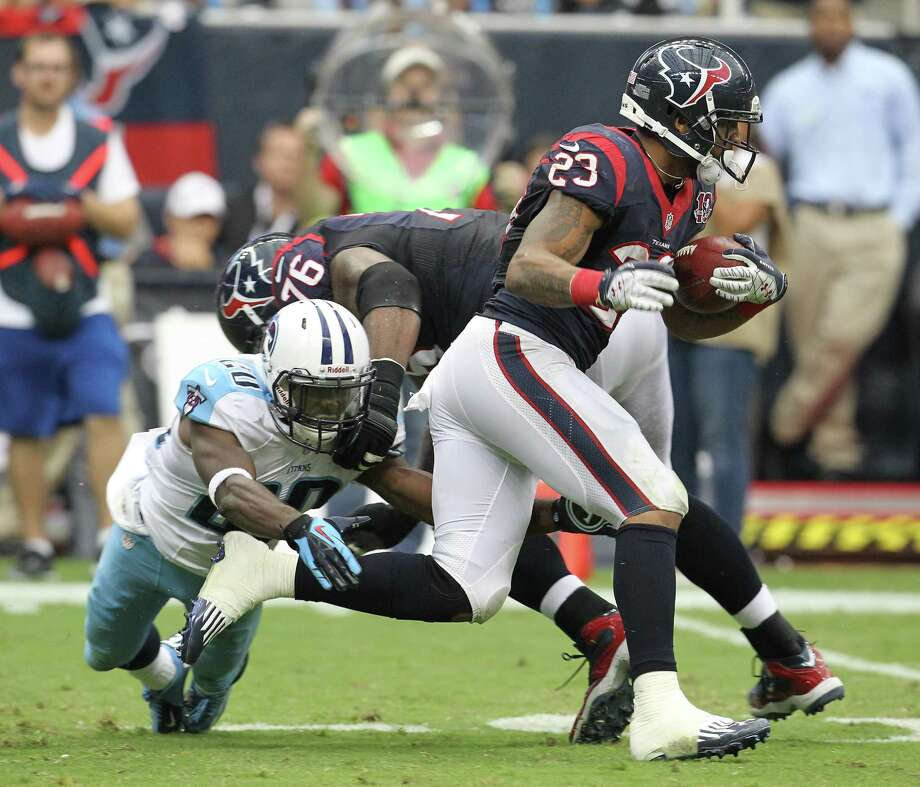 Houston Texans running back Arian Foster (23) gains yards as Tennessee Titans cornerback Alterraun Verner (20) tries to get a hand on him during the second quarter at Reliant Stadium on Sunday, Sept. 30, 2012, in Houston. Photo: Karen Warren, Houston Chronicle / © 2012  Houston Chronicle