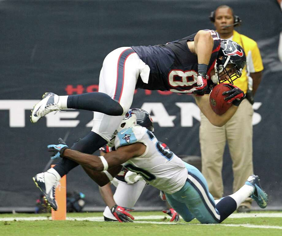 Houston Texans tight end Owen Daniels (81) dives over Tennessee Titans cornerback Alterraun Verner (20) as he goes into the end zone for a touchdown during the third quarter at Reliant Stadium on Sunday, Sept. 30, 2012, in Houston. Photo: Karen Warren, Houston Chronicle / © 2012  Houston Chronicle