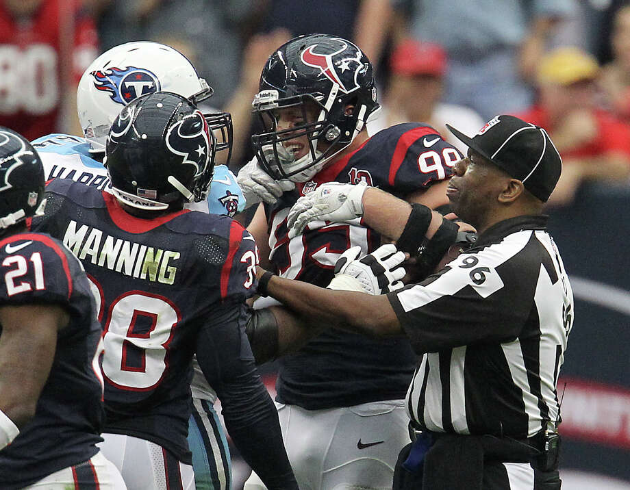 Houston Texans defensive end J.J. Watt (99) tussles with Tennessee Titans guard Leroy Harris (64) as a referee tries to break them up during the third quarter at Reliant Stadium on Sunday, Sept. 30, 2012, in Houston. Photo: Karen Warren, Houston Chronicle / © 2012  Houston Chronicle