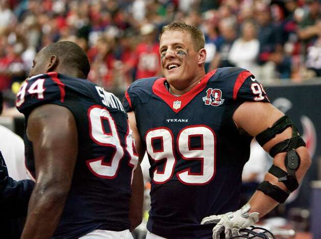 Houston Texans defensive end J.J. Watt (99) jokes with Houston Texans defensive end Antonio Smith (94) as the offense takes the field during the third quarter at Reliant Stadium on Sunday, Sept. 30, 2012, in Houston. The Houston Texans won 38-14. Photo: Nick De La Torre, Houston Chronicle / © 2012  Houston Chronicle