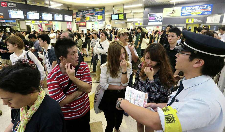 A station employee (R) answers customer enquiries about disruptions to the train service caused by Typhoon Jelawat at a railway station in Tokyo on September 30, 2012. Powerful Typhoon Jelawat made landfall on September 30 on the Japanese mainland a day after hitting southern Okinawa island, where local media said it left one dead and some 140 people injured.  JAPAN OUT   AFP PHOTO / JIJI PRESSJIJI PRESS/AFP/GettyImages Photo: JIJI PRESS, AFP/Getty Images / AFP
