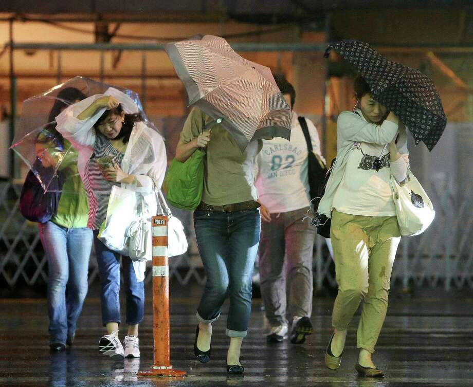 People cross a road a they try to hold on to their umbrellas under heavy winds and rain brought on by Typhoon Jelawat in front of a railway station in Tokyo on September 30, 2012. Powerful Typhoon Jelawat made landfall on September 30 on the Japanese mainland a day after hitting southern Okinawa island, where local media said it left one dead and some 140 people injured.   JAPAN OUT AFP PHOTO / JIJI PRESSJIJI PRESS/AFP/GettyImages Photo: JIJI PRESS, AFP/Getty Images / AFP
