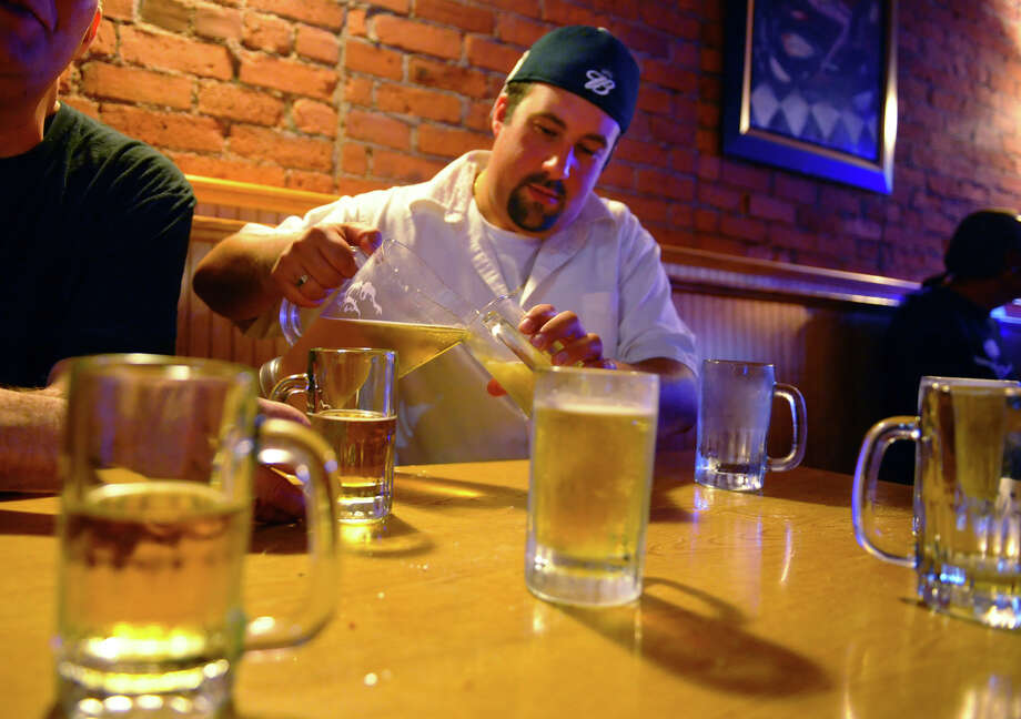 Alphonse Criscuolo, of East Haven, enjoys some beer with coworkers after work at Porky's Cafe on Center Street in downtown Shelton, Conn. on Tuesday September 26, 2012. Photo: Christian Abraham / Connecticut Post