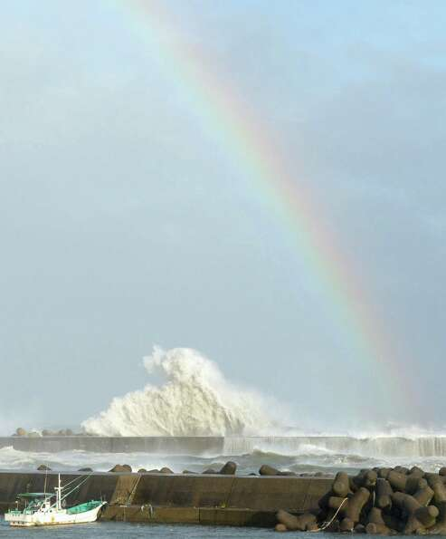 A rainbow appears while high waves hit a breakwater in Kihocho, Mie prefecture, western Japan Sunday