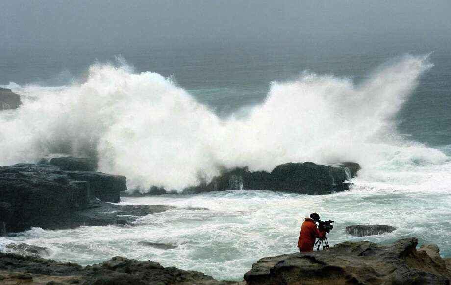High waves hit a rocky shore as a TV cameraman films the scene in Shirahama, Wakayama Prefecture, central Japan, Sunday afternoon, Sept. 30, 2012. Powerful Typhoon Jelawat  is heading to Tokyo after injuring dozens of people, causing blackouts and paralyzing traffic in southern Japan. (AP Photo/Kyodo News) JAPAN OUT, MANDATORY CREDIT, NO LICENSING IN CHINA, FRANCE, HONG KONG, JAPAN AND SOUTH KOREA Photo: Associated Press / Kyodo News