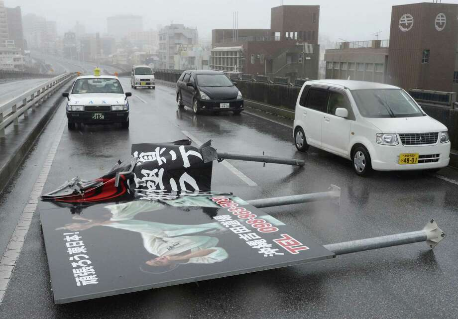 An advertising billboard blown away by wind lies on a road in Naha as Typhoon Jelawat hit the southern Japanese prefecture of Okinawa Saturday, Sept. 29, 2012. (AP Photo/Kyodo News) JAPAN OUT, MANDATORY CREDIT, NO LICENSING IN CHINA, FRANCE, HONG KONG, JAPAN AND SOUTH KOREA Photo: Associated Press / Kyodo News
