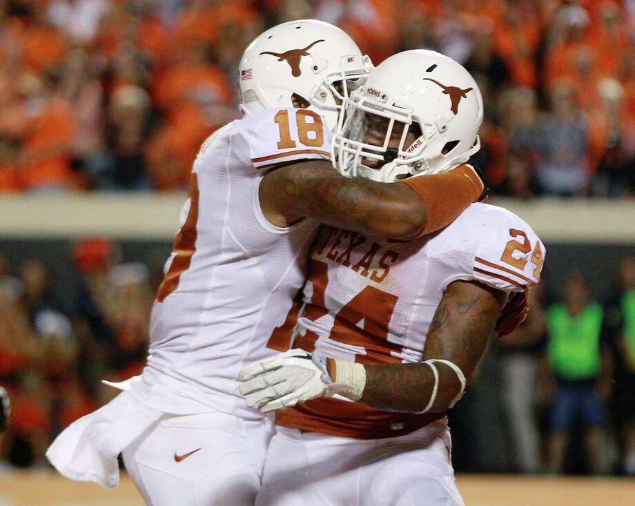 Texas right end D.J. Grant (18) and running back Joe Bergeron (24) celebrate Bergeron's touchdown against Oklahoma State in the fourth quarter of an NCAA college football game in Stillwater, Okla., Saturday, Sept. 29, 2012. Texas won 41-36. (AP Photo/Sue Ogrocki) Photo: Sue Ogrocki, Associated Press / AP