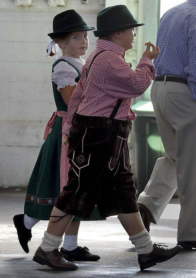 Dressed in German garb, Chloe Coldiron (left) and Ben McPhee survey Oktoberfest, where everyone is German for a day. Photo: Brant Ward, The Chronicle