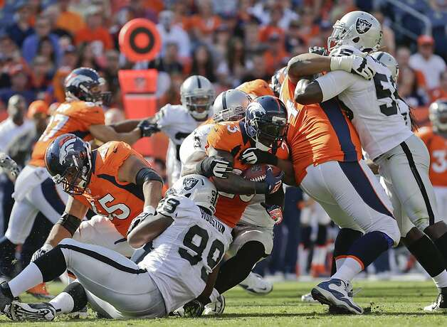 Denver Broncos running back Willis McGahee (23) is tackled by Oakland Raiders defensive end Lamarr Houston (99) during the third quarter of an NFL football game, Sunday, Sept. 30, 2012, in Denver. (AP Photo/Joe Mahoney) Photo: Joe Mahoney, Associated Press