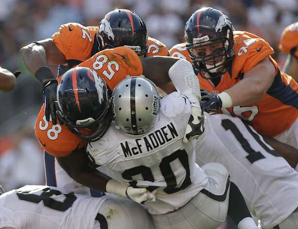 Oakland Raiders running back Darren McFadden (20) is stopped by Denver Broncos outside linebacker Von Miller (58), defensive end Mitch Unrein (96) and outside linebacker Wesley Woodyard (52) during the third quarter of an NFL football game, Sunday, Sept. 30, 2012, in Denver. (AP Photo/Joe Mahoney) Photo: Joe Mahoney, Associated Press