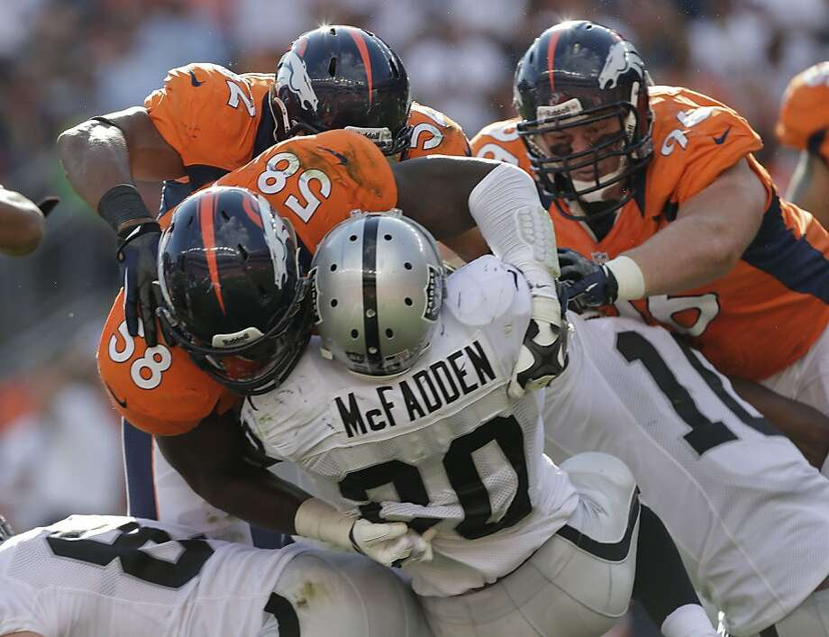 Raiders running back Darren McFadden is stuffed by linebacker Von Miller (58) and a wall of his Denver teammates. Photo: Joe Mahoney, Associated Press