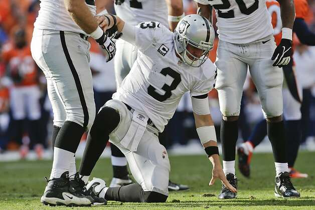 Oakland Raiders quarterback Carson Palmer (3) is helped up off the turf after taking a hit by the Denver Broncos during the fourth quarter of an NFL football game, Sunday, Sept. 30, 2012, in Denver. The Broncos won 37-6. (AP Photo/Joe Mahoney) Photo: Joe Mahoney, Associated Press