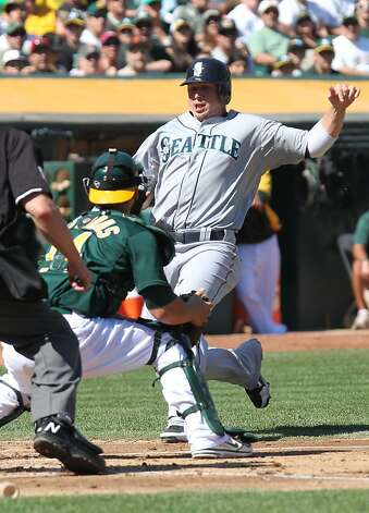 Oakland Athletics catcher George Kottaras tags out Seattle Mariners Justin Smoak in the second inning of their MLB baseball game with the Sunday September 30, 2012 in Oakland California Photo: Lance Iversen, The Chronicle