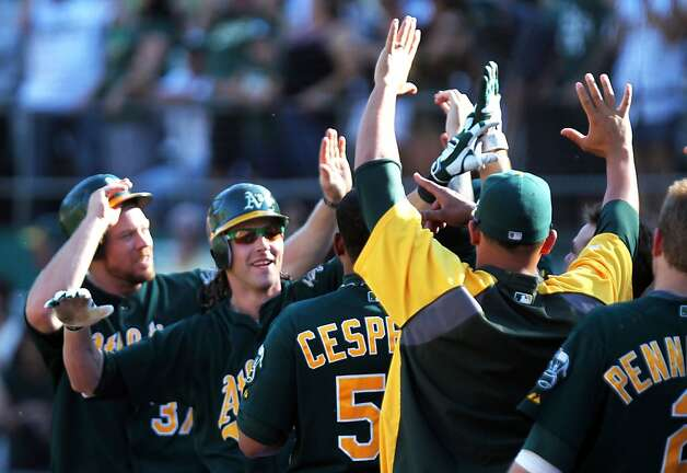 Oakland Athletics Josh Reddick second from left, celebrates his two run home run against the Seattle Mariners in the 8th inning of their MLB baseball game with the Sunday September 30, 2012 in Oakland California. A's win 5-2 Photo: Lance Iversen, The Chronicle