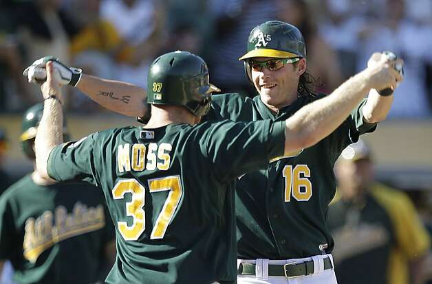 Oakland Athletics' Josh Reddick (16) and Brandon Moss (37) celebrate after Reddick hit a two-run home run off Seattle Mariners' Lucas Luetge in the eighth inning of a baseball game Sunday, Sept. 30, 2012, in Oakland, Calif. (AP Photo/Ben Margot) Photo: Ben Margot, Associated Press
