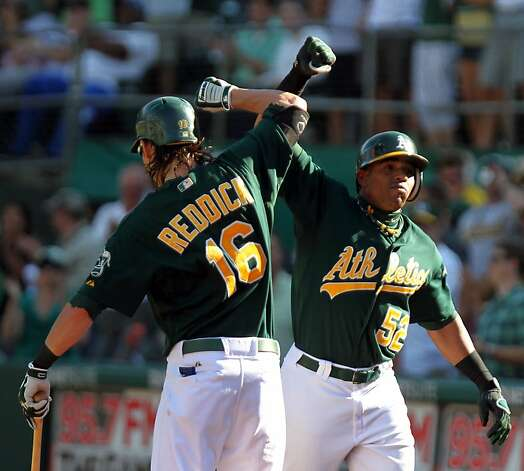 Oakland Athletics Yoenis Cespedes (52) celebrates his go ahead solo home run with Josh Reddick against the Seattle Mariners in the 8th inning of their MLB baseball game with the Sunday September 30, 2012 in Oakland California. A's win 5-2. Photo: Lance Iversen, The Chronicle