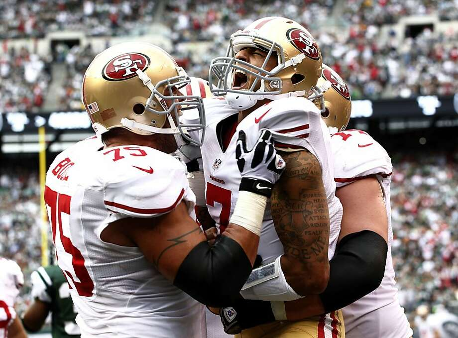 Colin Kaepernick (center) celebrates with Alex Boone (left) and Joe Staley after his 7-yard touchdown run against the Jets. Photo: Jeff Zelevansky, Getty Images