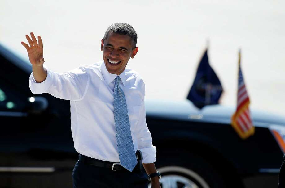 President Barack Obama waves to supporters as he arrives at McCarran International Airport in Las Vegas on Sunday. Photo: Isaac Brekken / FR159466 AP