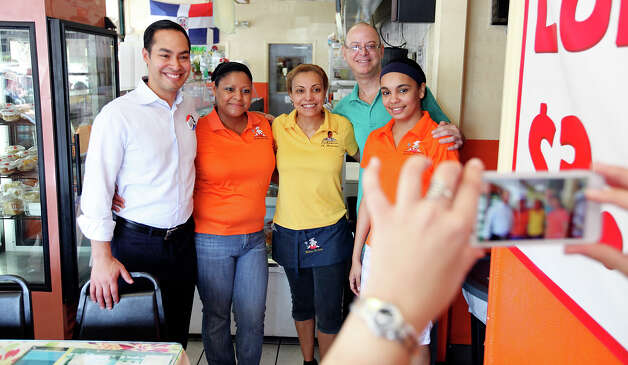 Mayor Julián Castro (from left) poses for photos with Lechonera El Barrio Restaurant employee Lucy Orellana, co-owner Julia Vasquez, employee Juan Vasquez, and employee Antonia Reyes during rally Sunday Sept. 30, 2012 at Lechonera El Barrio Restaurant in Orlando, FL.  Castro helped energize volunteers for the Obama For America campaign. Scores of volunteers fanned out through Orlando neighborhoods to talk to potential voters about re-electing the president and register new voters. Castro thanked the volunteers, who headed back out to continue their work leading up to Oct. 9, the last day to register voters. Photo: Edward A. Ornelas, Express-News / © 2012 San Antonio Express-News