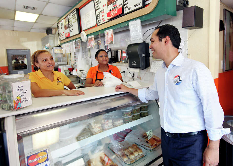 Lechonera El Barrio Restaurant co-owner Julia Vasquez (from left) and restaurant employee Lucy Orellana talk with Mayor Julián Castro during a rally Sunday Sept. 30, 2012 at the restaurant in Orlando, FL.  Castro helped energize volunteers for the Obama For America campaign. Scores of volunteers fanned out through Orlando neighborhoods to talk to potential voters about re-electing the president and register new voters. Castro thanked the volunteers, who headed back out to continue their work leading up to Oct. 9, the last day to register voters. Photo: Edward A. Ornelas, Express-News / © 2012 San Antonio Express-News