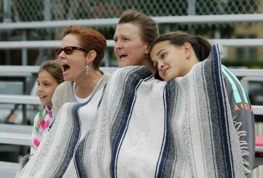 Hannah Kinder, 7, left, Whitney Bogardus, Anne Tulek and her daughter, Elysa, 13, right, brace against the cooler weather at a Little League game Sunday. Photo: Melissa Phillip / © 2012 Houston Chronicle