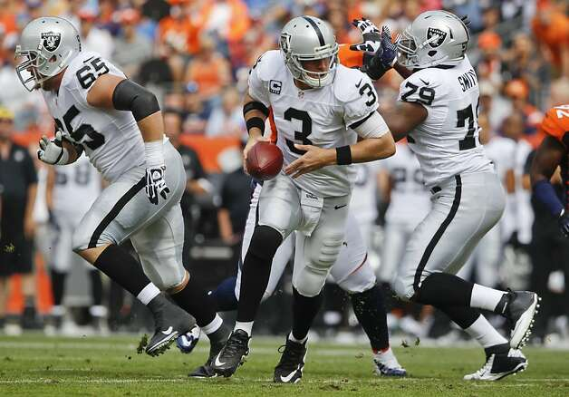 Oakland Raiders quarterback Carson Palmer looks to hand off the football against the Denver Broncos during the first quarter of an NFL football game, Sunday, Sept. 30, 2012, in Denver. (AP Photo/David Zalubowski) Photo: David Zalubowski, Associated Press