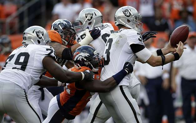 Denver Broncos Elvis Dumervil (92) against Oakland Raiders Carson Palmer (3) during the fourth quarter of an NFL football game, Sunday, Sept. 30, 2012, in Denver. (AP Photo/Joe Mahoney) Photo: Joe Mahoney, Associated Press