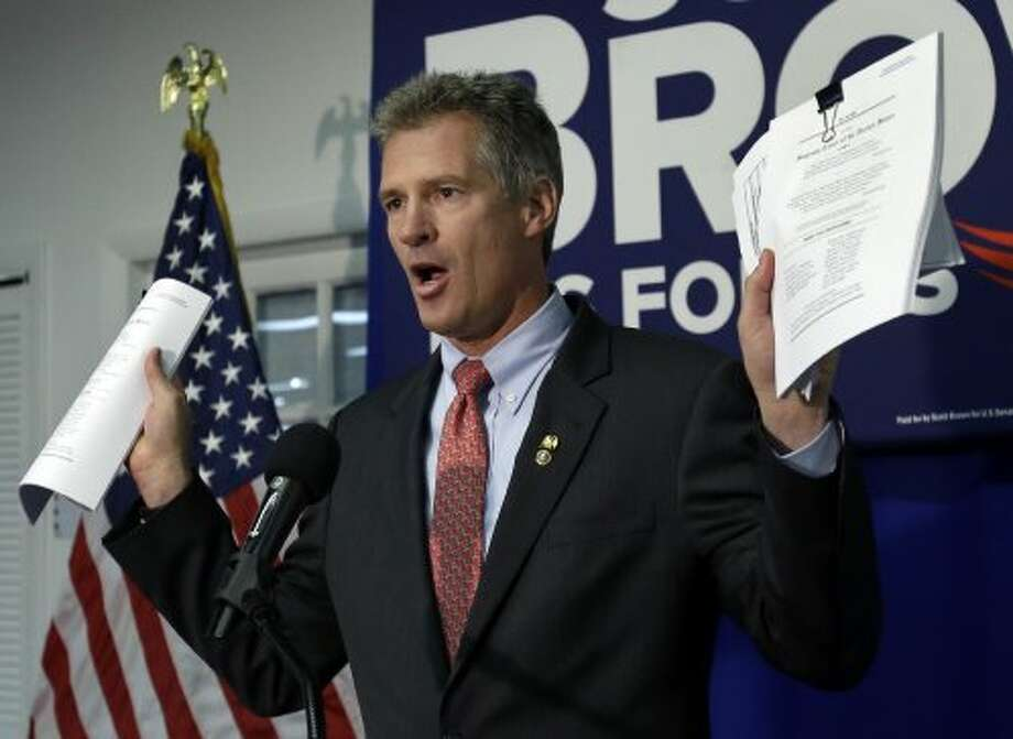 "Republican incumbent U.S. Sen. Scott Brown, R-Mass., holds up paperwork during a news conference in Boston Friday, Sept. 21, 2012 as he criticized Democratic challenger Elizabeth Warren's role in a case involving victims of asbestos poisoning. Brown charges that the Harvard Law School professor was paid nearly $250,000 by Travelers Insurance to help get the company ""off the hook"" for hefty asbestos settlements. (Elise Amendola / Associated Press)"