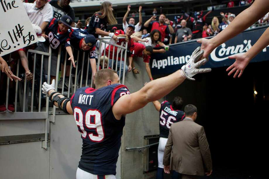 Texans defensive end J.J. Watt  slaps hands with fans as he leaves the field after the Texans beat the Titans. Photo: Brett Coomer, Houston Chronicle / © 2012  Houston Chronicle