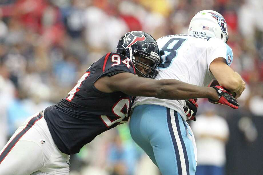 Texans defensive end Antonio Smith sacks Titans quarterback Matt Hasselbeck during the fourth quarter. Photo: Karen Warren, Houston Chronicle / © 2012  Houston Chronicle
