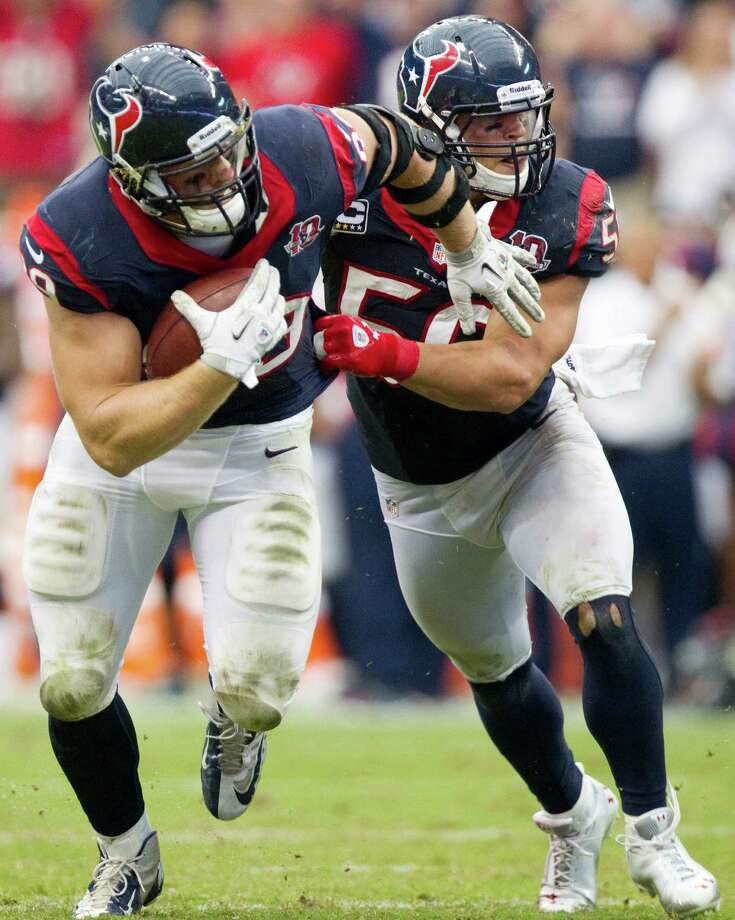 Texans defensive end J.J. Watt is pushed by linebacker Brian Cushing as he picks up a fumble by Titans quarterback Matt Hasselbeck. Photo: Brett Coomer, Houston Chronicle / © 2012  Houston Chronicle