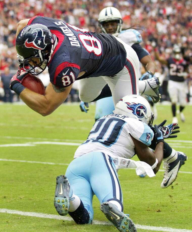 Texans tight end Owen Daniels dives over Titans cornerback Alterraun Verner for a 28-yard touchdown during the third quarter. Photo: Brett Coomer, Houston Chronicle / © 2012  Houston Chronicle