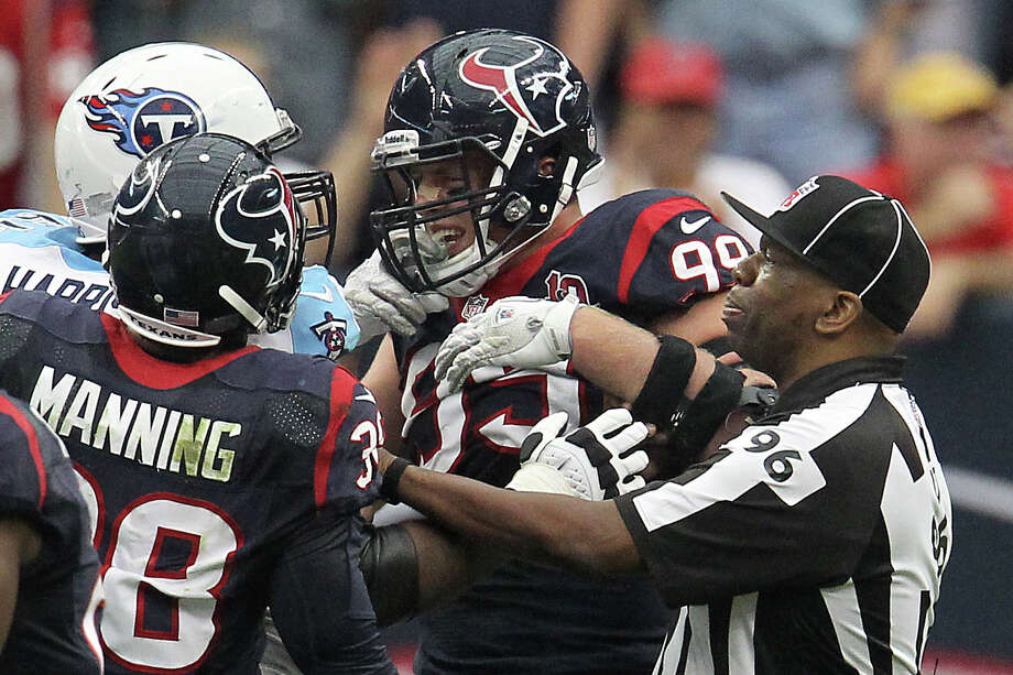 Texans defensive end J.J. Watt (99) tussles with Titans guard Leroy Harris (64) as a referee tries to break them up during the third quarter. Photo: Karen Warren, Houston Chronicle / © 2012  Houston Chronicle