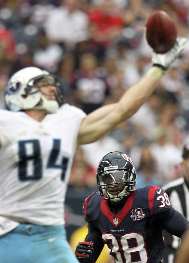 Texans free safety Danieal Manning (38) keeps an eye on a ball he intercepted after it was tipped by Titans tight end Taylor Thompson (84). Photo: Nick De La Torre, Houston Chronicle / © 2012  Houston Chronicle