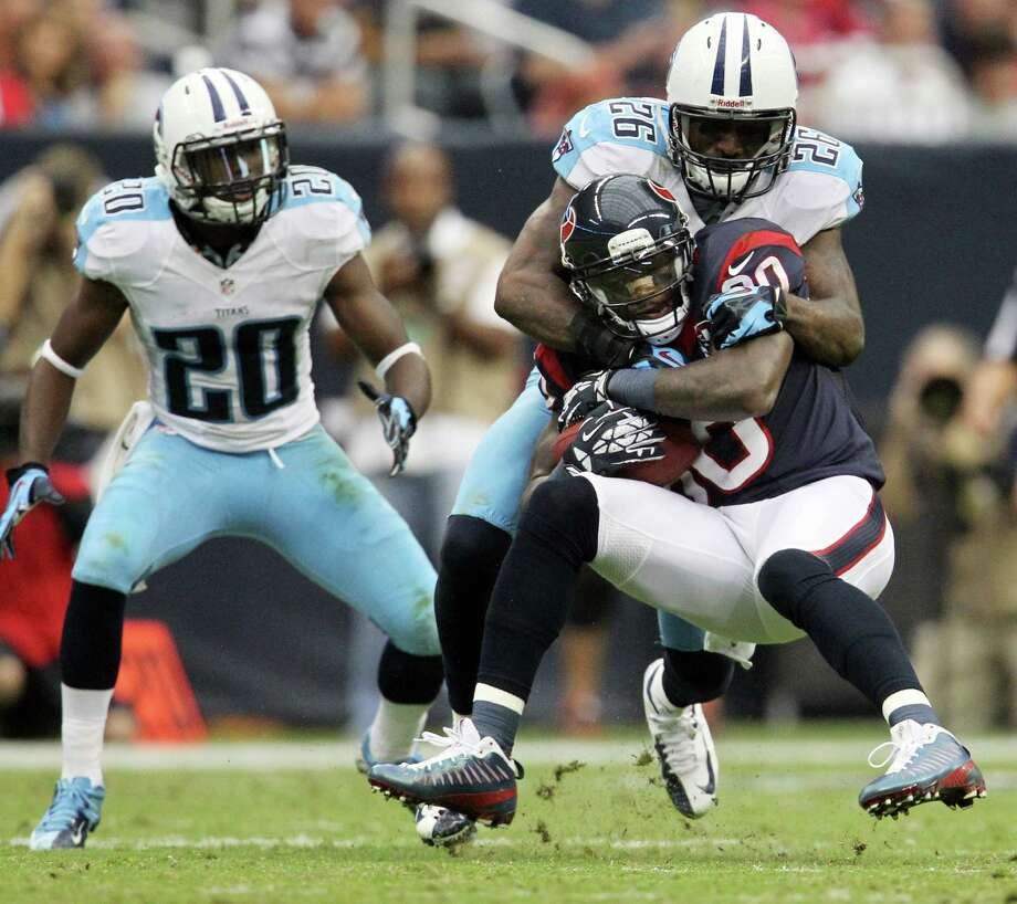 Titans strong safety Jordan Babineaux (26) tackles Houston Texans wide receiver Andre Johnson (80) during the second quarter. Photo: Karen Warren, Houston Chronicle / © 2012  Houston Chronicle