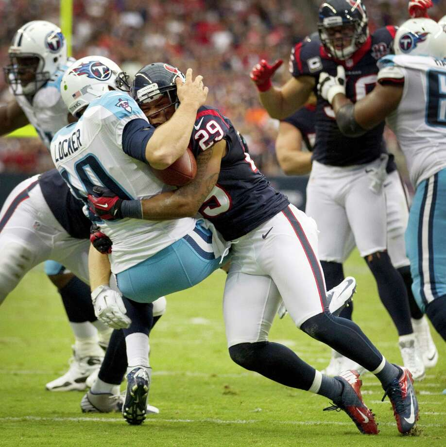 Texans strong safety Glover Quin (29) sacks Titans quarterback Jake Locker (10) during the first quarter. Locker was injured on the play and left the game. Photo: Brett Coomer, Houston Chronicle / © 2012  Houston Chronicle