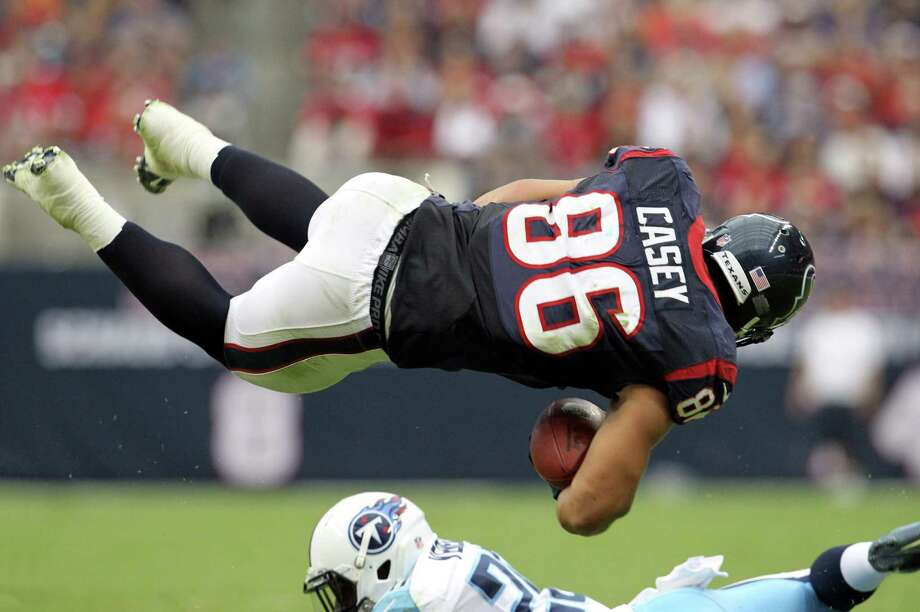 Texans fullback James Casey (86) is upended by Titans cornerback Alterraun Verner (20) during the first quarter. Photo: Karen Warren, Houston Chronicle / © 2012  Houston Chronicle