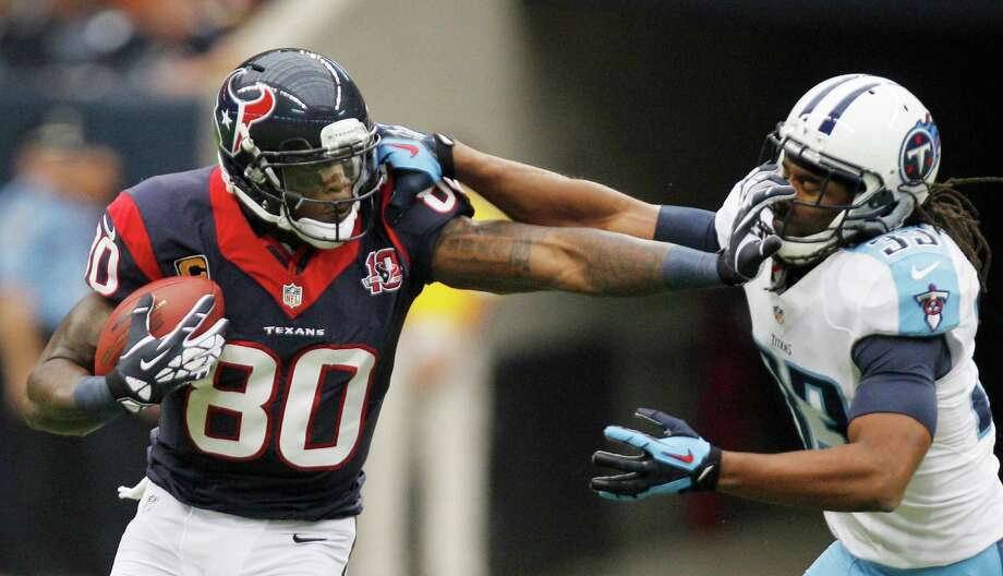 Texans wide receiver Andre Johnson (80) fends of Titans free safety Michael Griffin (33) during the first quarter. Photo: Brett Coomer, Houston Chronicle / © 2012  Houston Chronicle