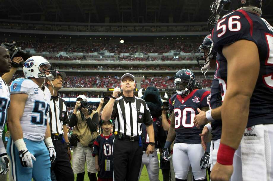 Referee Carl Cheffers, center, performs the pregame coin toss before the Houston Texans faced the Tennessee Titans at Reliant Stadium. Photo: Brett Coomer, Houston Chronicle / © 2012  Houston Chronicle