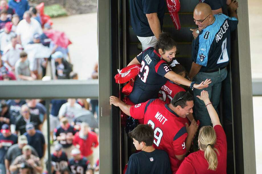 Texans fans exchange high fives as the ride escalators into the stadium to watch their team face the Tennessee Titans. Photo: Smiley N. Pool, Houston Chronicle / © 2012  Houston Chronicle