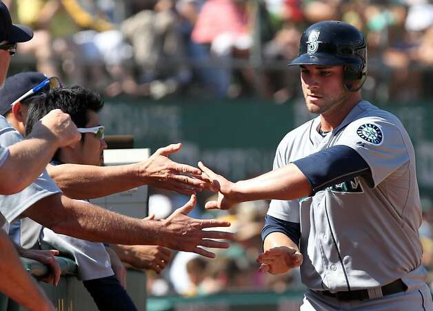 Seattle Mariners Casper Wells is greeted at the dugout after scoring the tying run off a base hit by Justin Smoak in the third inning of their MLB baseball game with the Oakland Athletics Sunday September 30, 2012 in Oakland California Photo: Lance Iversen, The Chronicle
