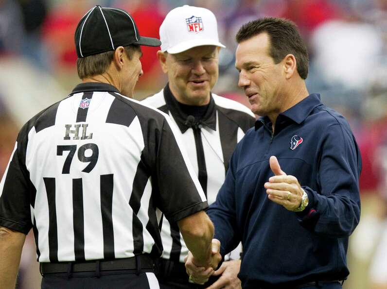 Texans head coach Gary Kubiak, right, greets head linesman  Kent Payne (79) and referee Carl Cheffer
