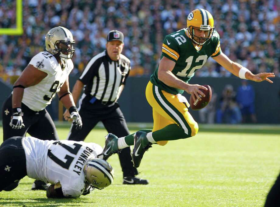 Green Bay Packers quarterback Aaron Rodgers gets tripped up by New Orleans Saints defensive tackle Brodrick Bunkley as defensive end Will Smith watches during the first half of an NFL football game Sunday, Sept. 30, 2012, in Green Bay, Wis. (AP Photo/Mike Roemer) Photo: Mike Roemer