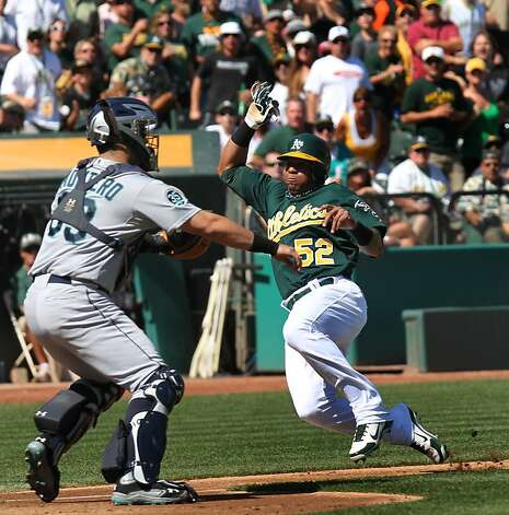 Oakland Athletics Yoenis Cespedes slides safely into home under the tag by Seattle Mariners catcher Jesus Montero in the first inning of their MLB baseball game with the Sunday September 30, 2012 in Oakland California Photo: Lance Iversen, The Chronicle