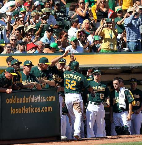 Oakland Athletics Yoenis Cespedes is congratulated by his teammates after scoring against the Seattle Mariners in the first inning of their MLB baseball game with the Sunday September 30, 2012 in Oakland California Photo: Lance Iversen, The Chronicle