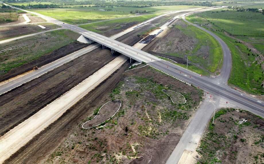 A smaller road crosses over the still-under-construction Texas 130 between Lockhart and Seguin this summer. An extension from south Austin to Seguin is the state's first public-private toll road to open to traffic. Photo: William Luther / © 2012 San Antonio Express-News