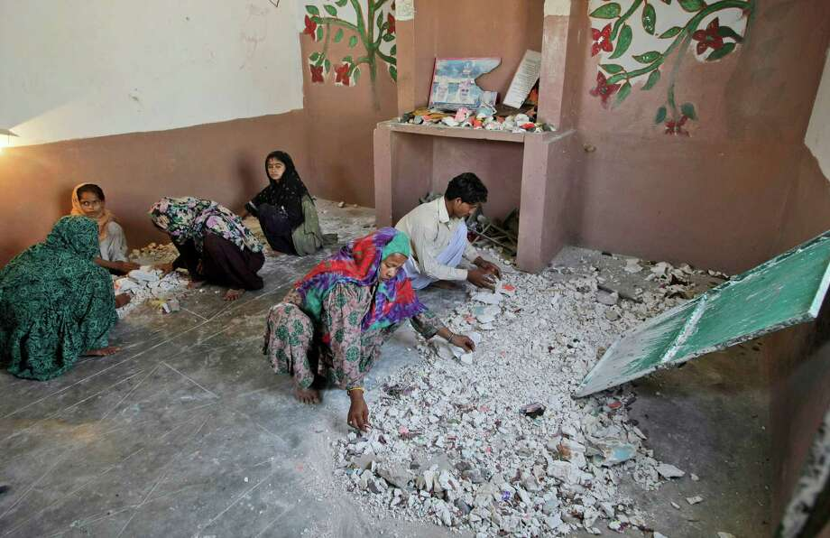 Hindus clean a temple after being attacked by a group of Muslim men in Karachi, Pakistan, Sunday, Sept. 30, 2012. A group of Muslims suspected of ransacking a Hindu temple in southern Pakistan may be charged with blasphemy, police said Sunday. The case is a rare twist on the use of the country's harsh blasphemy laws, which are more often invoked against supposed offenses to Islam as opposed to minority faiths. (AP Photo/Fareed Khan) Photo: Fareed Khan / AP
